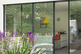 View from Garden Through Sliding Patio Doors to Modern Kitchen Beyond, London Photo by Pedro Silmon
