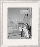 Roy Takeno (Editor) and Group Reading Manzanar Paper [I.E. Los Angeles Times] in Front of Office Prints by Ansel Adams