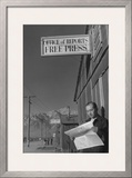 Roy Takeno Reading Paper in Front of Office Posters by Ansel Adams