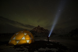 Adventurer Standing under the Stars Next to a Tent and Looking at Auroras Photographic Print by Chad Copeland