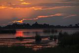 The Sun Setting over the Okavango Delta Photographic Print by Beverly Joubert