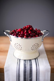 Bright Red Cranberries in Cream Colored Strainer. Sitting on Vintage Striped Linen on Butcher Block Photographic Print by Craig Holmes