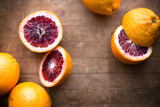Blood Oranges Whole and Sliced on a Rustic Wood Cutting Board Photographic Print by Craig Holmes