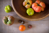 Variety of Heirloom Tomatoes in a Rustic Bowl and on a Light Wood Surface Photographic Print by Craig Holmes