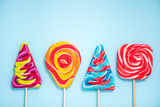 Colorful Vibrant Lollipops, Flat Lay on Blue Background Photographic Print by Marcin Jucha