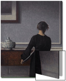 Interior with Young Woman from Behind Posters by Vilhelm Hammershoi