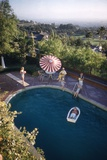 A Family at their Backyard Swimming Pool, in Foreground a Floating Rowboat with Boy Aboard Photographic Print by Frank Scherschel