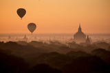 Hot Air Balloons Float Above the Terraces of a Buddhist Temple in Bagan Photographic Print by Cory Richards