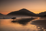 A Surfer Makes His Way Out of the Water at Sunset on Praia Do Itamambuca in Brazil Photographic Print by Alex Saberi