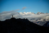 A Mountaineer Stands on a Mountaintop with Higher Peaks Visible in the Sunlight Beyond Photographic Print by Cory Richards
