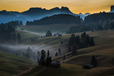 A small village on rolling hills as the sun rises over the Dolomites, Italy