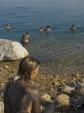 Woman's Back Covered with Mud and People Floating in the Sea in Background, Dead Sea, Israel
