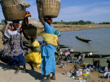 Women with Baskets of Laundry on Their Heads Beside the River, Djenne, Mali, Africa