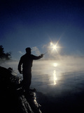 Silhouette of Fisherman Casting a Line into Lake, Ontario, Canada