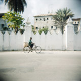 Man on Bicycle with Old Buildings Behind, Stone Town, Zanzibar, Tanzania, East Africa, Africa