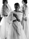 Three Models Wearing White Mink Stoles over Long Evening Dresses