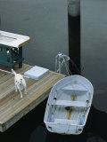 A Dog Waits on a Dock Near a Small Row Boat