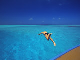 Man Jumping into Tropical Sea from Deck, Maldives, Indian Ocean
