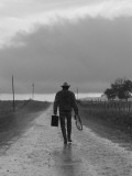 Silhouette of Cowboy Walking on Empty Road