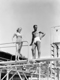 A Man and a Young Woman Stand on a Diving Board in Their Bathing Suits