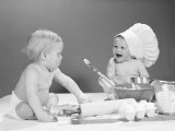 Two Babies With Mixing Bowls and Rolling Pins, One Wearing Chef's Hat, Flour on Faces