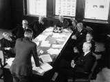 Elderly Businessmen at Conference Table With Man Standing and Talking
