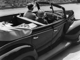 Backview of a Man Driving a Sedan Convertible With Luggage
