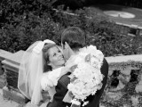Smiling Bride Holding Bouquet of Daisies Embracing Groom