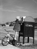 Girl Standing on Tricycle on Suburban Sidewalk, Mailing Letter in Mailbox