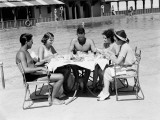 Group of People Sitting Poolside at Hotel, Eating Dinner, Miami, Florida