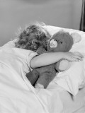Little Girl Asleep in Bed, With Arm Around Teddy Bear