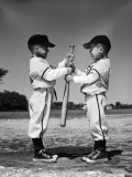 Two Boys in Little League Uniforms, Facing Each Other, Holding Baseball Bat