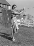Woman in Apron Smiling As She is Hanging Laundry on Clothesline