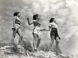 Three Women Standing on Beach, Holding Hands, Smiling