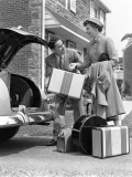 Smiling Couple Load Suitcases Into Trunk of Sedan