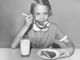 Girl (8-9) Sitting at Table, Eating Pie, Portrait