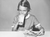 Girl (8-9) Sitting at Table, Drinking Milk, Portrait