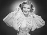 Woman in Evening Dress Combing Hair in Studio