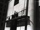 Man Working on Platform Hanging From Building