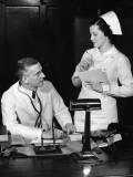 Nurse Confers W/Doctor at His Desk