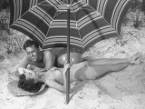 Young Couple Under Beach Umbrella