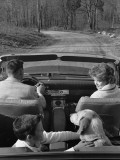 Family Driving in Convertible Along Country Road