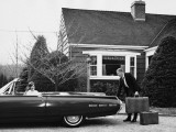 Man Loading Trunk With Suitcases While Woman Waits in Car