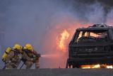 Firefighters Hosing a Burning Car