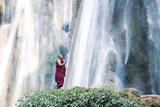 Myanmar, Mandalay Division, Pyin Oo Lwin. Burmese Monk Praying under Dattawgyaik Waterfall (Mr)