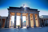Germany, Berlin. Cyclists Passing under the Brandenburg Gate