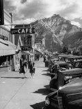 Pedestrians Walking Along Main Street in Resort Town with Cascade Mountain in the Background Lámina fotográfica por Andreas Feininger