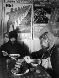 Russian Workers Eating Black Bread and Soup at Table with Soviet Communist Workers Posters, Siberia 写真プリント : マーガレット・バーク=ホワイト
