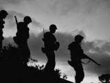 Four Soldiers with Helmets and Rifles Moving on Crest of Ridge, on Patrol at Night Fotografie-Druck von Michael Rougier