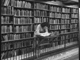 Woman Reading Book Among Shelves on Balcony in American History Room in New York Public Library プレミアム写真プリント : アルフレッド・アイゼンスタット